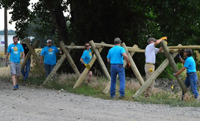 Volunteers from Faith Chapel work at installing a fence.